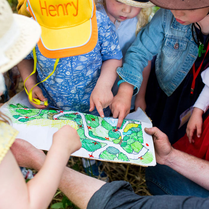 Paul showing children a map at a birthday party.