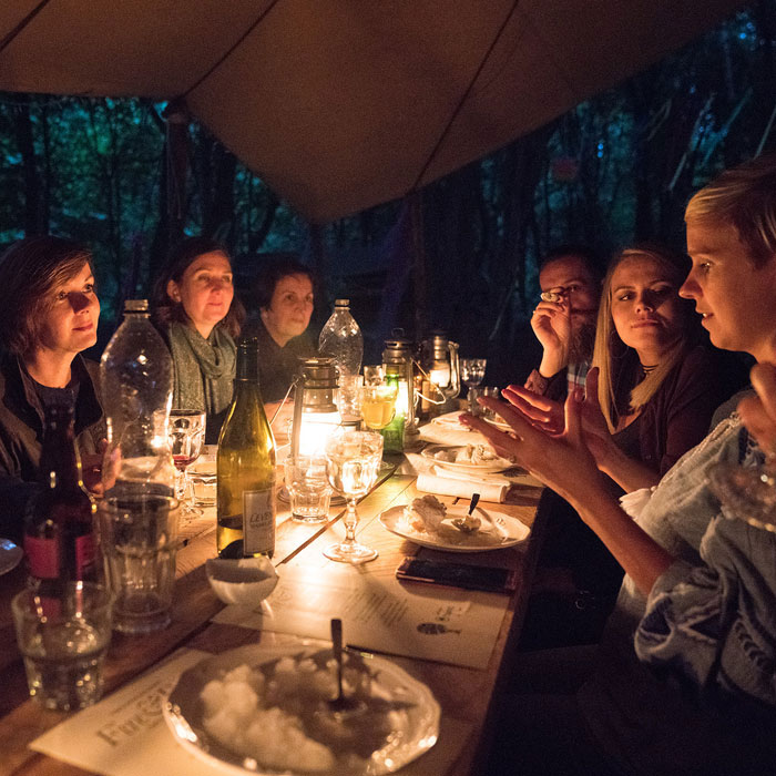People enjoying a unique dining experience at Fire & Dine in the woods.
