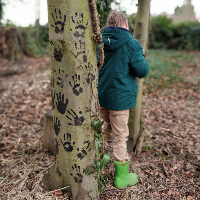 Child stood behind a tree after covering it in black hand prints
