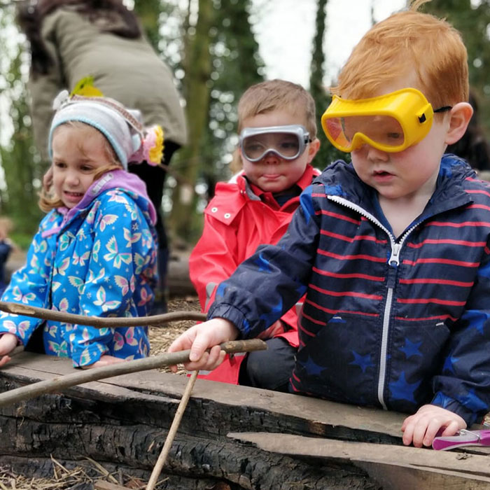 Children toasting marshmallows at Tree Nippers session.