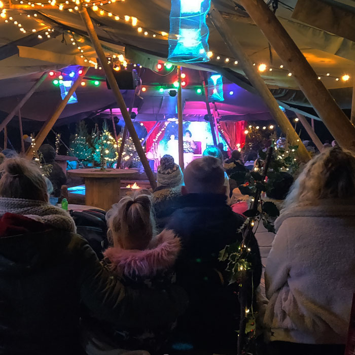 Family watching the pantomime in the woods.